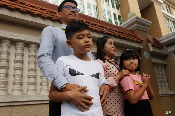 Journalist Yeang Sothearin stands together with his family in front of the municipal court, in Phnom Penh, Cambodia, Thursday,…