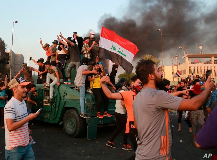 Anti-government protesters take over a security forces armored vehicle before they burn it during a demonstration in Baghdad, Iraq, Oct. 3, 2019.