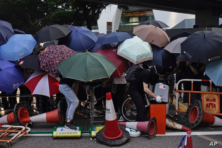 Protesters hide behind umbrellas as they form a barricade to block a road in Hong Kong, Oct. 4, 2019.