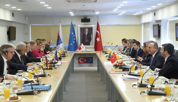 Heading their delegations, Turkey's Foreign Minister Mevlut Cavusoglu, 2nd right, and European Commissioner for Immigration Dimitris Avramopoulos, left, attend a meeting to discuss cooperation on migration management in Ankara, Turkey, Oct. 4, 2019.