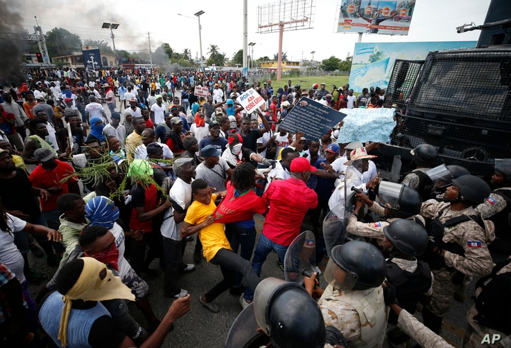 Demonstrators scuffle with the police during a protest calling for the resignation of President Jovenel Moise, near the airport…