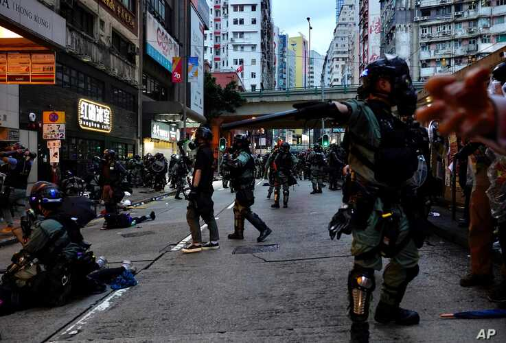"""Riot police tell journalists to leave while they arrest protesters in Hong Kong, Sunday, Oct. 6, 2019. Shouting """"Wearing mask…"""