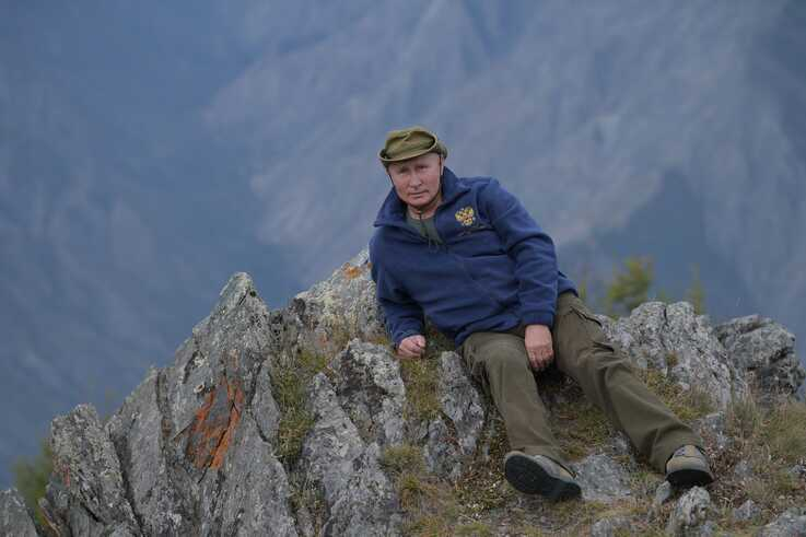 In this undated photo, Russian President Vladimir Putin rests on a hill in Siberia.