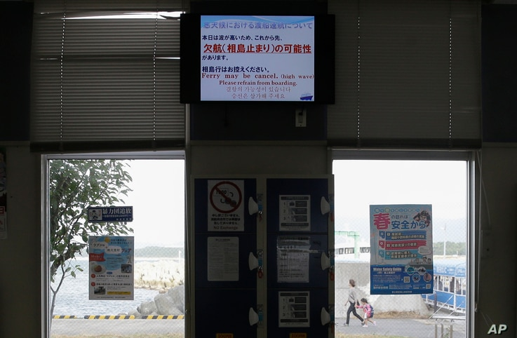 A ferry station shows a sign that cancels boat trips at the Shigu port in Fukuoka, southern Japan on Friday, Oct. 11, 2019. A…