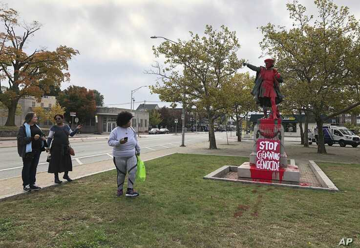 People stop to view red paint covering a statue of Christopher Columbus on Monday, Oct. 14, 2019, in Providence, R.I., after it was vandalized on the day named to honor him as one of the first Europeans to reach the New World.