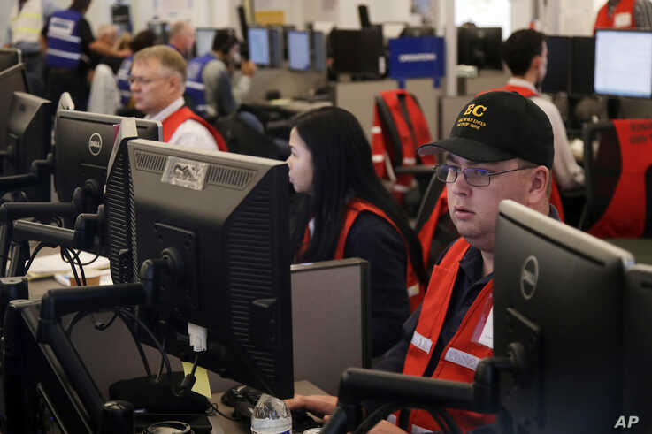 FILE - In this Oct. 10, 2019, file photo, Pacific Gas & Electric employees work in the PG&E Emergency Operations Center in San…