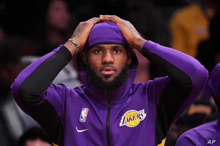 Los Angeles Lakers forward LeBron James sits on the bench during the first half of a preseason NBA basketball game against the Golden State Warriors, Oct. 14, 2019, in Los Angeles.