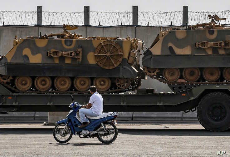 A motorist drives past a Turkish forces truck transporting armoured personnel carriers at the border with Syria in Karkamis,…