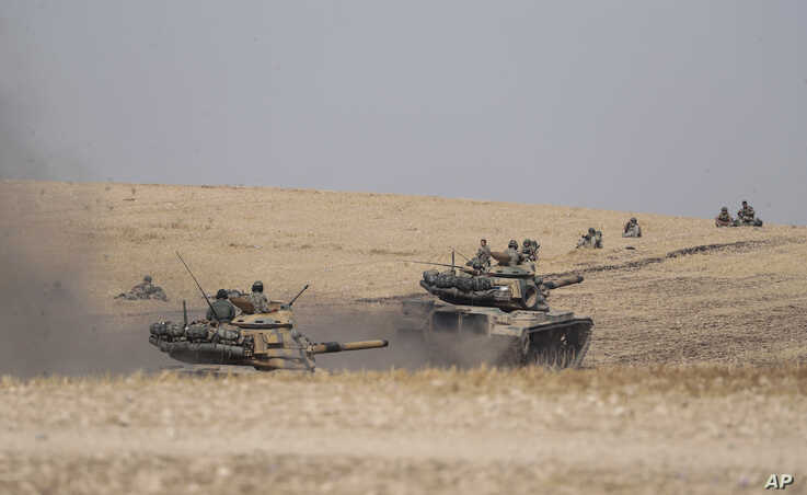 Turkish tanks and troops stationed near Syrian town of Manbij, Syria, Tuesday. Oct. 15, 2019. Russia moved to fill the void…