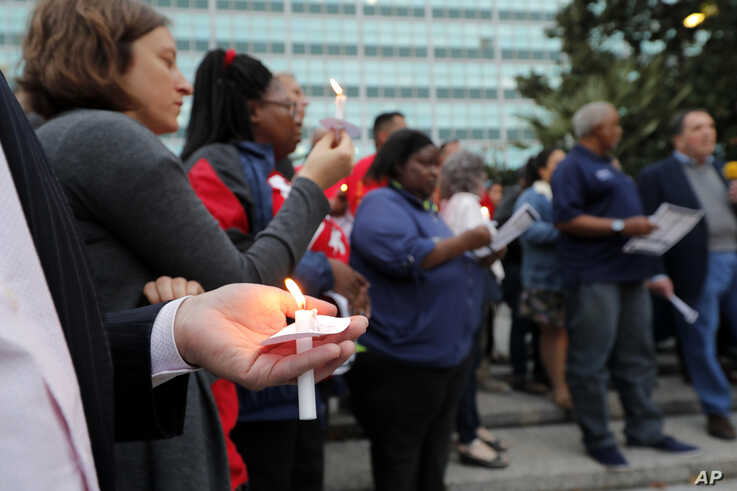 People hold candles during a candlelight vigil outside city hall for deceased and injured workers from the Hard Rock Hotel…