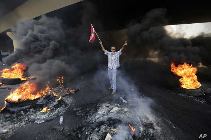 An anti-government protester makes victory sign, as he holds a Lebanese national flag and walks fire of tires that sits to…