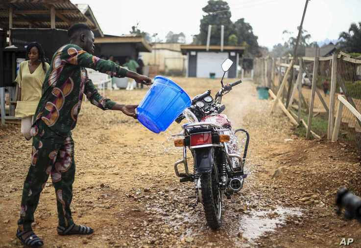 Motorcycle taxi driver Germain Kalubenge pours chlorinated water on his motorcycle after taking a suspected case of Ebola to an…
