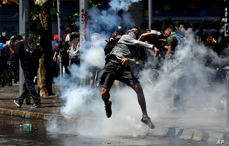 A protester returns a tear gas canister to police during clashes in Santiago, Chile, Monday, Oct. 21, 2019. Protests in the…