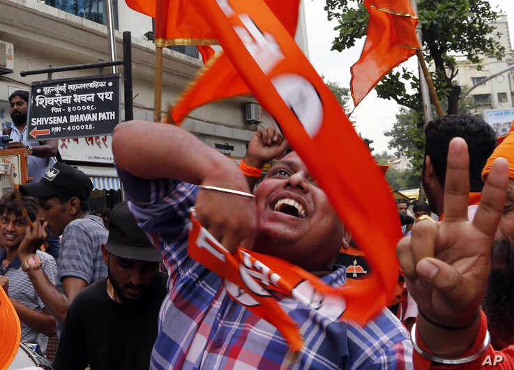 Shiv Sena party supporters celebrate outside their party office in Mumbai, India, Thursday, Oct. 24, 2019. According to…