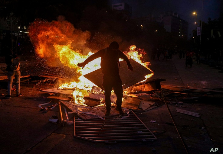 A wet anti-government protester dries his clothes by standing close to a burning street barricade, after police used a water cannon to disperse demonstrators in Santiago, Chile, Oct. 29, 2019.