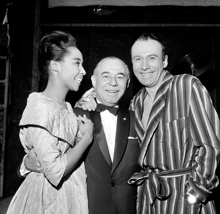 """Co-stars Diahann Carroll, left, and Richard Kiley flank composer Richard Rodgers backstage after the opening of """"No Strings"""" at…"""