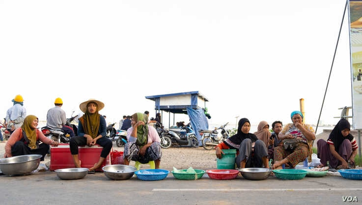 Khmer Islam fish sellers sit in front of Sokha ferrry entrance on the evening of Oct. 14, 2019, in Phnom Penh, Cambodia. (Malis Tum/VOA Khmer)