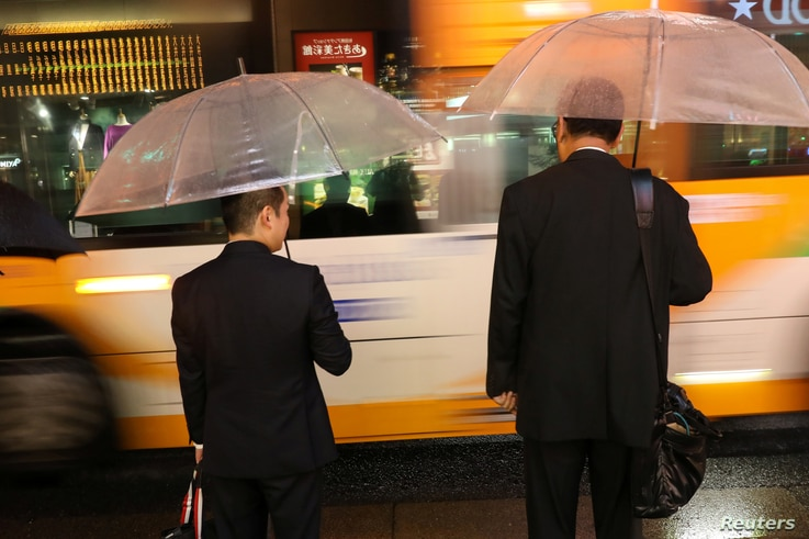 Commuters at rush hour during a rain storm near Shinagawa Station in Tokyo, Japan October 11, 2019. Typhoon Hagibis approached…