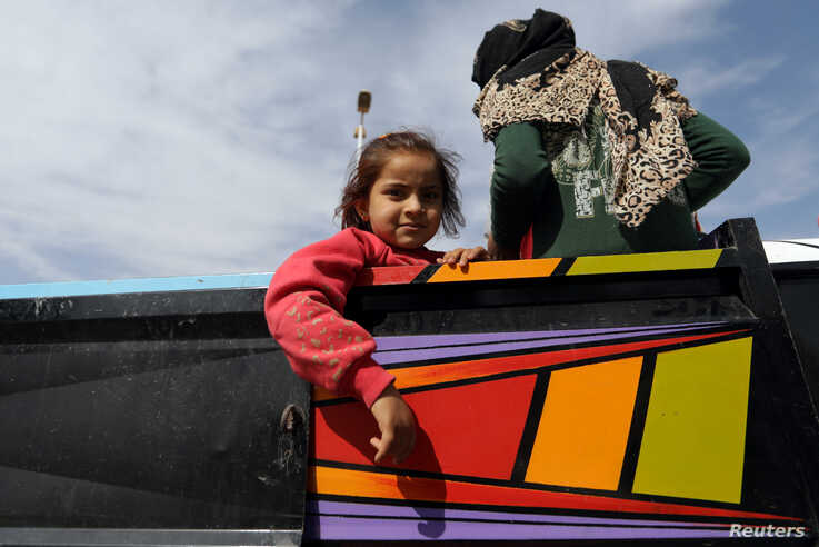 A girl is seen at a back of a truck in the border town of Tel Abyad, Syria, October 14, 2019. REUTERS/Khalil Ashawi -…