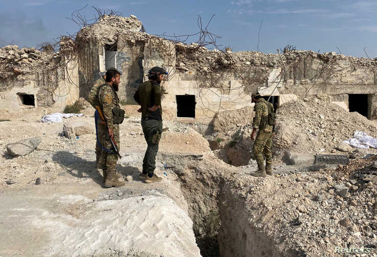 Turkey-backed Syrian rebel fighters stand near underground tunnels said to be made by the Syrian Democratic Forces (SDF) in Tal…