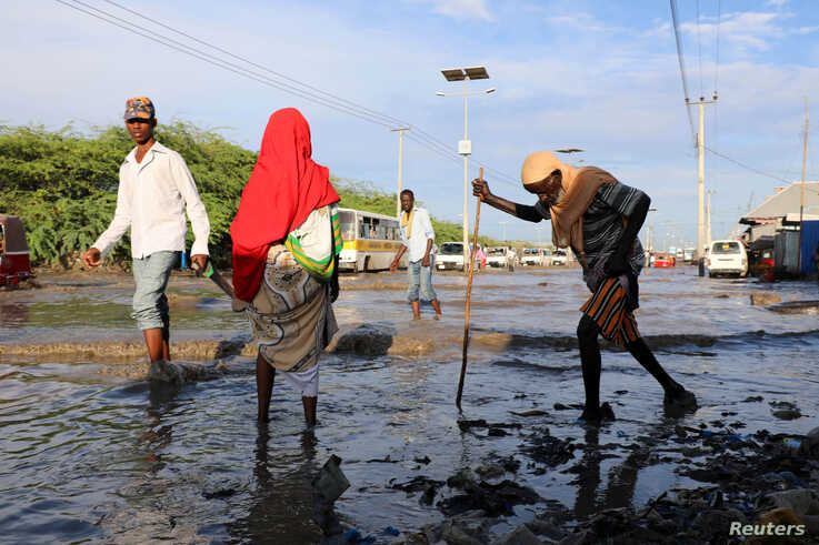Somalis wade through flood waters after heavy rain in Mogadishu, Somalia October 21, 2019. REUTERS/Feisal Omar - RC15AA28E9D0