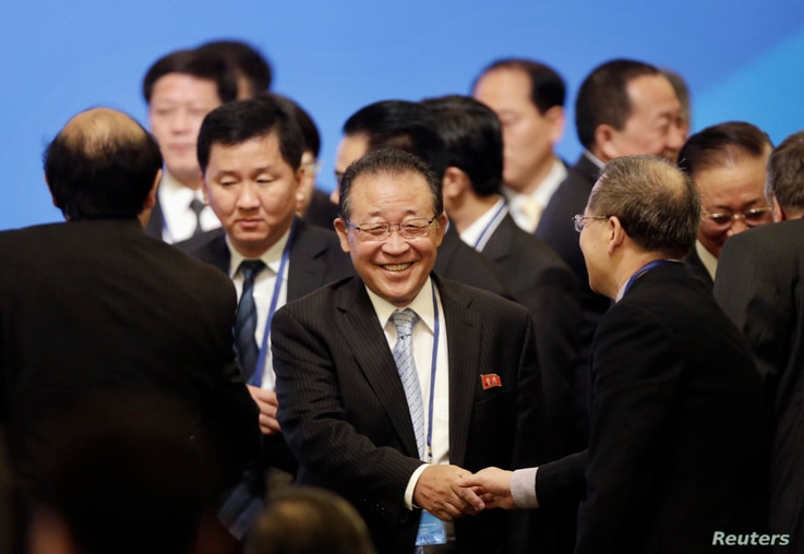 North Korea's First Vice Foreign Minister and envoy to the six-party talks Kim Kye-gwan (C ) shakes hands with a delegate as he…