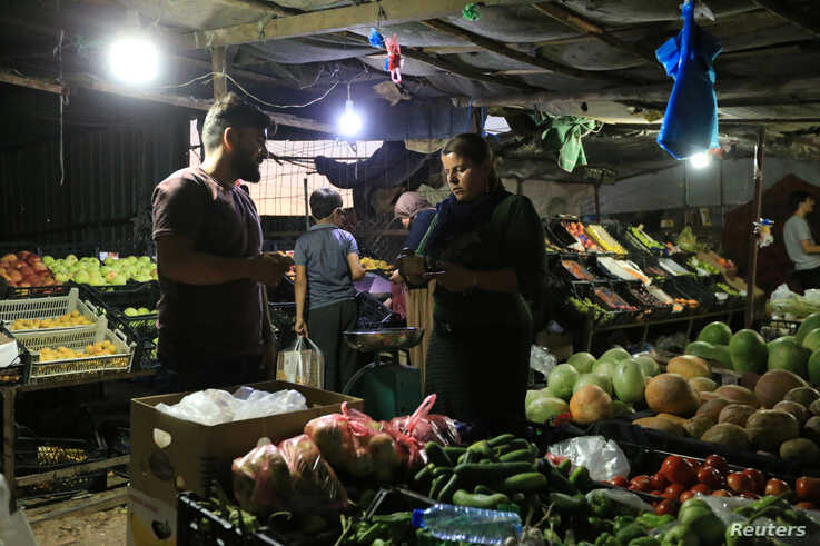 A displaced Iraqi woman from the minority Yazidi sect, who fled the Iraqi town of Sinjar, buys vegetables at the Khanki camp on…