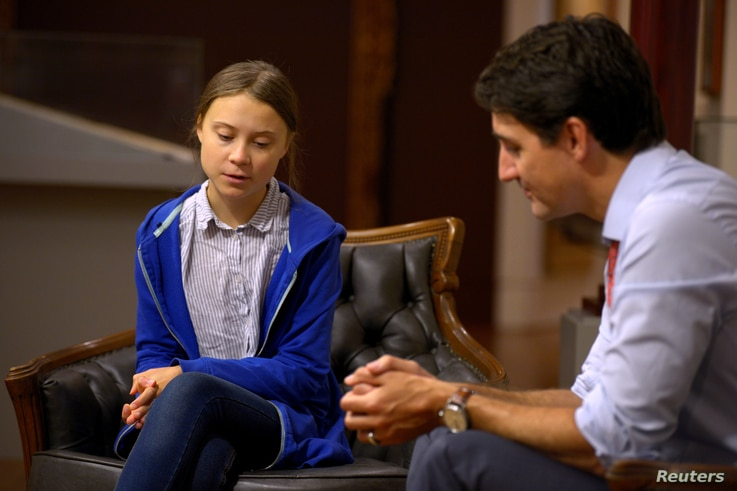 FILE - Canada's Prime Minister Justin Trudeau greets Swedish climate change teen activist Greta Thunberg before a climate strike march in Montreal, Quebec, Canada, Sept. 27, 2019.