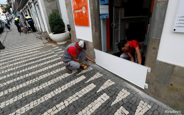 Two workers install a protection board before the arrival of Hurricane Lorenzo in Angra do Heroismo in the Azores islands, Portugal, Oct. 1, 2019.