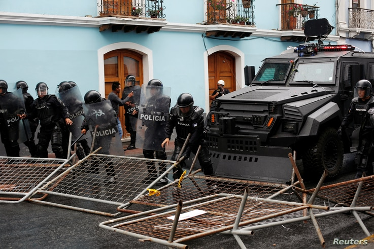 Riot police move barricades set up by demonstrators during a protest after Ecuadorian President Lenin Moreno's government ended four-decade-old fuel subsidies, in Quito, Ecuador, Oct. 3, 2019.