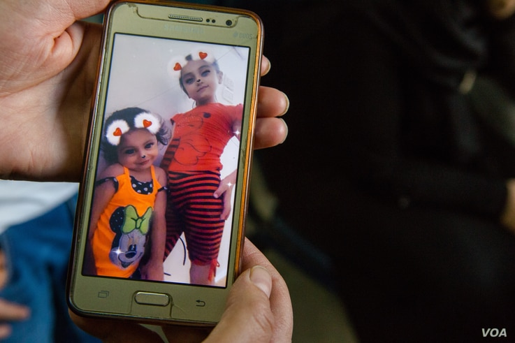 Relatives show pictures of Sara and her younger sister Zainab, before the children were struck recently by a bomb. Oct. 15, 2019, in Qamishli, Syria. (Y. Boechat/VOA)