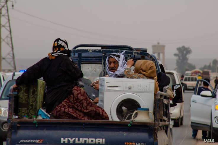 Families flee on the road from Ras al-Ayn the day before Kurdish-led forces pull out of the city, pictured in the outskirts of Ras al-Ayn, Syria, Oct. 19, 2019. (Yan Boechat/VOA)
