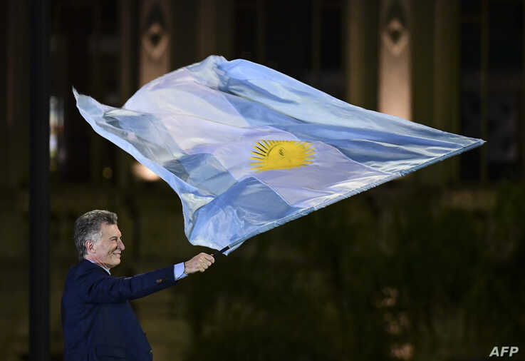 Argentina's President and presidential candidate of the Juntos por el Cambio party Mauricio Macri waves a national flag during the closing rally of his campaign in Cordoba, Argentina, Oct. 24, 2019.