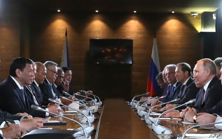 Russian President Vladimir Putin (R) and Philippine's President Rodrigo Duterte, both flanked by officials, are seen meeting in Sochi, Russia, Oct. 3, 2019.