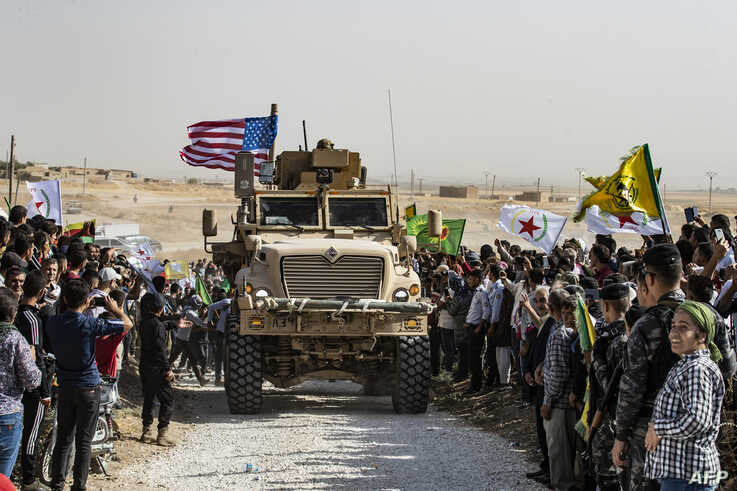Syrian Kurds gather around a U.S. armored vehicle during a demonstration against Turkish threats on the outskirts of Ras al-Ain town in Syria's Hasakeh province near the Turkish border, Oct. 6, 2019.