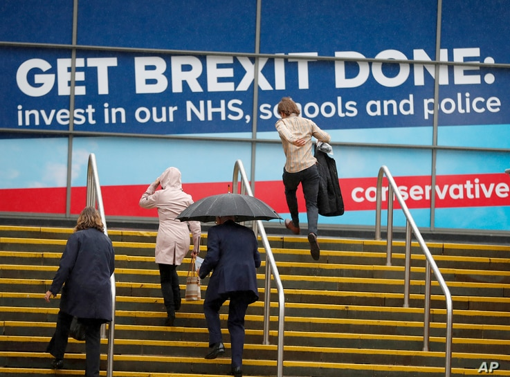 Delegates arrive in heavy rain at the Conservative Party Conference in Manchester, England, Oct. 1, 2019.