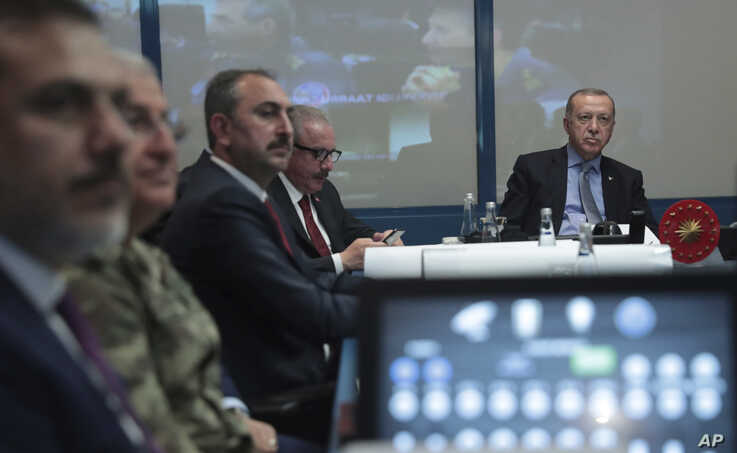 Turkey's President Recep Tayyip Erdogan, right, with military and Intelligence chiefs, ministers and his ruling party members in an operations room at the presidential palace, in Ankara, Turkey, Oct. 9, 2019.