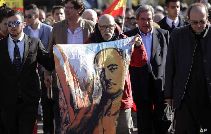A man holds a depiction of the late Spanish dictator Gen. Francisco Franco as people gather outside Mingorrubio's cemetery, on the outskirts of Madrid, Spain, Oct. 24, 2019.