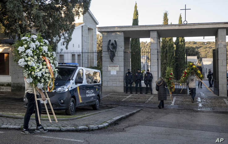 People carry wreath of flowers at Mingorrubio's cemetery, on the outskirts of Madrid, Spain, Oct. 24, 2019. Forty-four years after his death, the remains of Spanish dictator Gen. Francisco were exhumed from his resting place and taken to a small family crypt.
