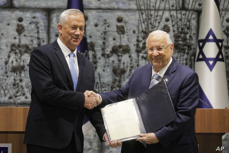 Israeli President Reuven Rivlin, right, hands a mandate to form new government to Blue and White Party leader Benny Gantz, in Jerusalem, Oct. 23, 2019.
