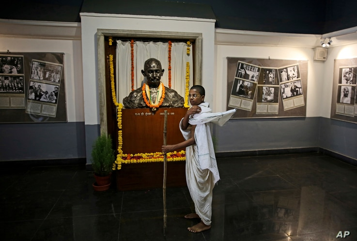 A school boy dressed as Mahatma Gandhi stands next to a bust of Gandhi at Gandhi museum on the eve of his 150th birth anniversary in New Delhi, India, Oct. 1, 2019.