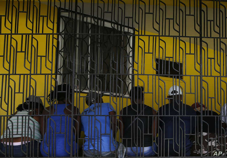 People wait in a long line to get out money at a financial institution in Leogane, Haiti, Oct. 5, 2019.