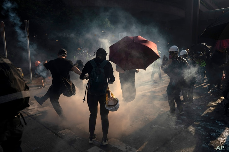 A demonstrator kicks back an exploded tear gas shell in Hong Kong, Oct. 1, 2019, during an escalation of protests in the semi-autonomous Chinese territory.
