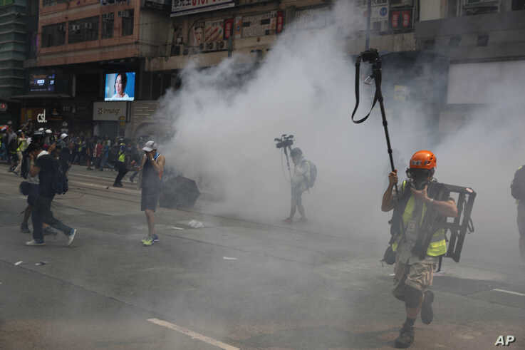 FILE - Journalists make their way through tear gas in Hong Kong, Sept. 29, 2019.