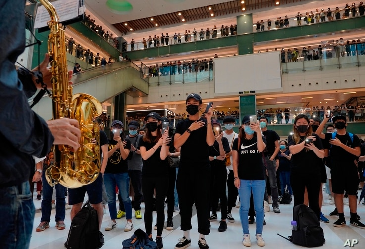 Protesters wearing masks in defiance of a recently imposed ban on face coverings perform at a shopping mall in Hong Kong, Oct.13, 2019.