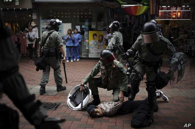 An anti government protester is detained by police at Tseun Wan, Hong Kong, Oct.13, 2019.