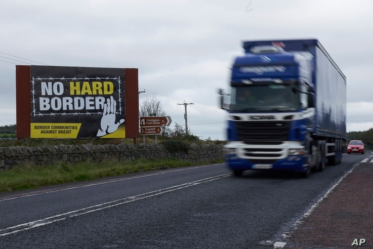 A truck races past a sign against the reestablishment of a hard border between Northern Ireland and the Republic of Ireland, Oct. 1, 2019.