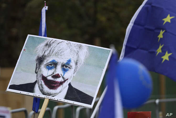 "Brexit opponents hold a placard showing Prime Minister Boris Johnson portrayed as the Joker as they take part in a ""People's Vote"" protest march calling for another referendum on Britain's EU membership, in London, Oct. 19, 2019."