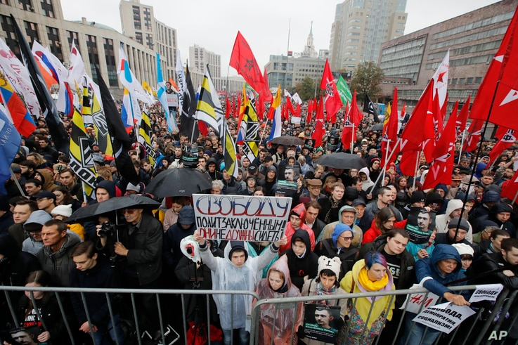 """FILE - A protester holds a banner reading """"Freedom to political prisoners!"""" during a rally in Moscow, Russia, Sept. 29, 2019."""