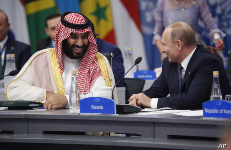 FILE - Saudi Arabia's Crown Prince Mohammed bin Salman talks with Russian President Vladimir Putin during a G-20 session with other heads of state, in Buenos Aires, Argentina, Nov. 30, 2018.